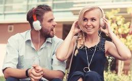 L'homme avec la femme apprécient la musique extérieure avec le fond urbain, defocused photographie stock