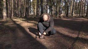 L'homme avec la hausse colle sur les chaussures sportives attachées par chemin banque de vidéos