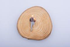 L'homme avec la jambe estropiée sur un rondin en bois a coupé dans les morceaux ronds Images stock