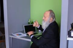 L'homme avec la longue barbe grise assimile de nouveaux instruments et s'assied dans le mod Photos libres de droits