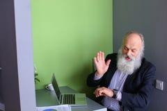L'homme avec la longue barbe grise assimile de nouveaux instruments et s'assied dans le mod Photos stock