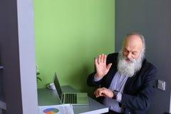 L'homme avec la longue barbe grise assimile de nouveaux instruments et s'assied dans le mod Images stock