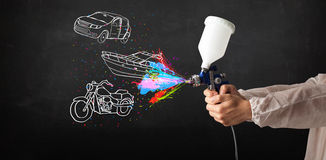 L'homme avec la peinture de jet d'aerographe avec la voiture, le bateau et la moto dessinent photo stock