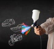 L'homme avec la peinture de jet d'aerographe avec la voiture, le bateau et la moto dessinent photographie stock