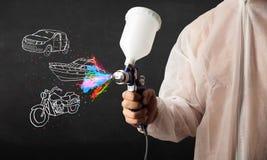 L'homme avec la peinture de jet d'aerographe avec la voiture, le bateau et la moto dessinent images libres de droits