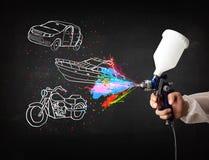 L'homme avec la peinture de jet d'aerographe avec la voiture, le bateau et la moto dessinent photos libres de droits