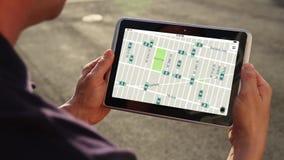 L'homme avec la tablette regarde l'animation de profils de trafic banque de vidéos