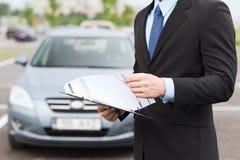 L'homme avec la voiture documente dehors Images stock