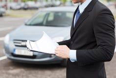 L'homme avec la voiture documente dehors photo stock
