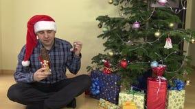 L'homme avec le chapeau rouge mangent du chocolat de forme de Santa avec satisfaction banque de vidéos