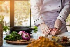 L'homme avec le couteau coupe la viande Image stock