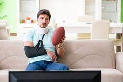 L'homme avec le football américain de observation de blessure de cou et de bras à la TV image libre de droits