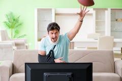 L'homme avec le football américain de observation de blessure de cou et de bras à la TV photos libres de droits