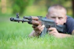 L'homme avec le fusil de kalachnikov a pris le but dehors image stock