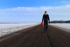 L'homme avec le gaz peut sur la route isolée en hiver Photo stock
