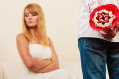 L'homme avec le groupe de sucrerie fleurit et femme malheureuse Photos stock