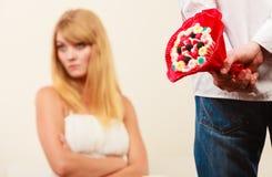 L'homme avec le groupe de sucrerie fleurit et femme malheureuse Photos libres de droits