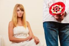 L'homme avec le groupe de sucrerie fleurit et femme malheureuse Image stock