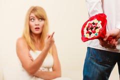 L'homme avec le groupe de sucrerie fleurit et femme malheureuse Photographie stock