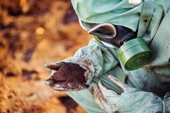 L'homme avec le masque de gaz et les vêtements militaires verts explore les barils af photos stock