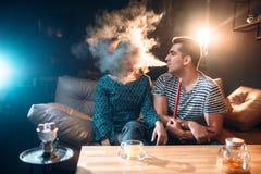 L'homme avec le narguilé, coups fument dans le visage de la femme photo stock