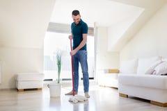L'homme avec le nettoyage de balai et de seau parquettent à la maison Images stock