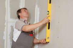 L'homme avec le niveau effectuent la rénovation Photo libre de droits
