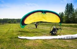 L'homme avec le parapentiste motorisé décolle d'un champ Photos libres de droits