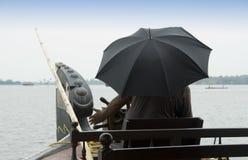L'homme avec le parapluie oriente une péniche aménagée en habitation Images libres de droits