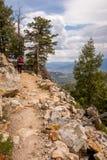 L'homme avec le sac à dos rouge augmente une traînée de montagne dans la forêt Photo libre de droits