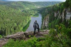 L'homme avec le sac à dos se tient sur la montagne Image stock