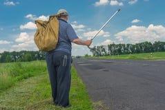 L'homme avec le sac se tenant sur un bord de la route tenant la marche collent  Images libres de droits