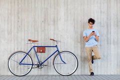 L'homme avec le smartphone et la vitesse fixe font du vélo sur la rue photographie stock
