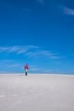 L'homme avec le surf des neiges passe par le désert Image libre de droits