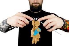 L'homme avec le tatouage et la participation de barbe a tricoté des aiguilles avec la silhouette tricotée de la femelle et du mâl Photos libres de droits
