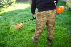 L'homme avec le trimmer fauche l'herbe dans la cour Jardinier avec la tondeuse à gazon photos stock