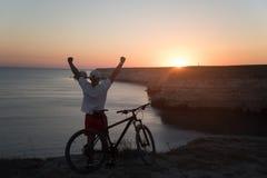 L'homme avec le vélo sur le bord de la mer Image stock