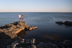 L'homme avec le vélo sur le bord de la mer Photographie stock libre de droits