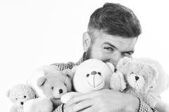L'homme avec le visage heureux tient la pile des jouets mous, fin  Le macho avec la barbe étreint beaucoup d'ours de nounours et  Photos stock
