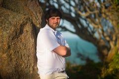 L'homme avec les cheveux noirs dans une chemise blanche s'est penché contre une pierre dans les bois au coucher du soleil Image libre de droits