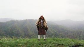 L'homme avec l'ours de barbe de moustache avec un tatouage tient le Caucasien de montagne clips vidéos