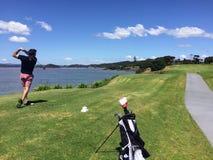 L'homme avec un gentil suivent en jouant le golf le long de la côte de n photos stock