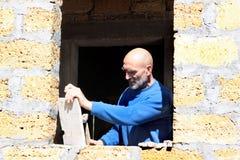 L'homme avec un marteau sur le bâtiment. Photographie stock libre de droits