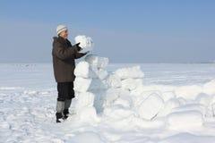 L'homme avec une barbe dans un chapeau gris construisant un igloo Photo stock