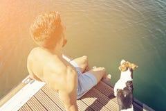 L'homme avec une barbe s'assied au bord du pilier avec un chien Image stock