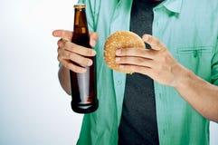 L'homme avec une barbe sur un fond blanc tient une bouteille de bière Photos libres de droits
