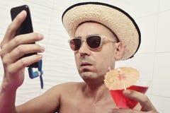 L'homme avec une fan s'est relié à son smartphone Photos stock