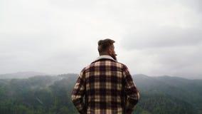 L'homme avec une moustache et une barbe sur la montagne regarde autour banque de vidéos