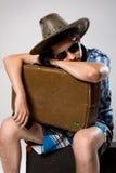 L'homme avec une valise attend l'appel téléphonique Image stock