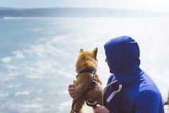 L'homme avec l'unité se reposante de petit de shiba chien japonais d'or d'inu sur une montagne et regarder l'horizon de mer bleu, photos stock